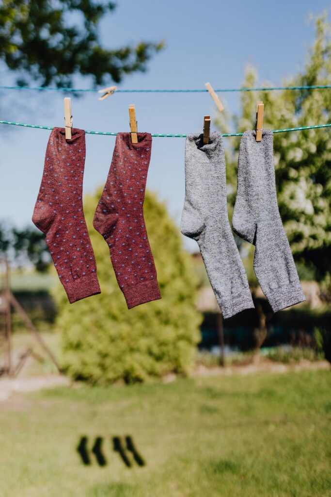 multicolored socks drying on rope with clothespins in garden